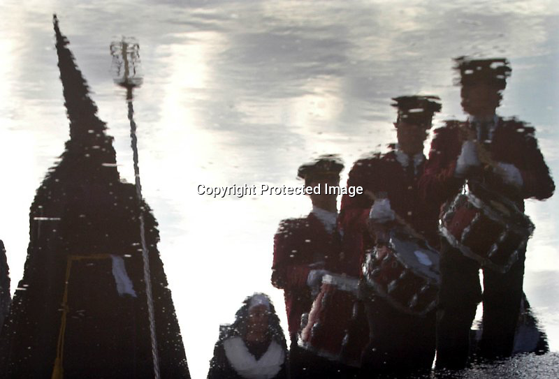 V. 02. Valencia, 09/04/2004. Un cofrades de la hermandad del Santísimo Cristo del Salvador y tres tamborileros se ven reflejados en un charco durante la procesión realizada a primera hora de la mañana para rezar en la orilla por los difuntos del mar y del 11-M. EFE/Kai Försterling