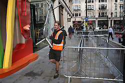 © Licensed to London News Pictures. 24/09/2015. London, UK. A workman carries a crowd barrier as customers camp out in a street next to the Apple Store in Regent Street. The iPhone 6s goes on sale at 8 am in the UK tomorrow. Photo credit: Peter Macdiarmid/LNP