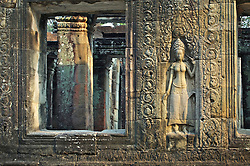 Closeup of wall and window structure showing gandharva carving and interior courtyard seen through window