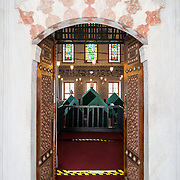 The tomb of Sultan Murad III in the cemetery of Hagia Sophia. Constructed in 1599, it has a hexagonal plan with a central dome supported by six columns. The center of the dome is decorated with the kalima-i tewhid in kufic style. Inside is decorated with coral-red Iznik tiles, mother-of-pearl, and ebony. The tomb includes the Sultan as well as his wife, Safiya Sultana, and his sons and daughters. The cemetery of Hagia Sophia, next to the main building, contains five tombs belonging to Ottoman Sultans and their family members.