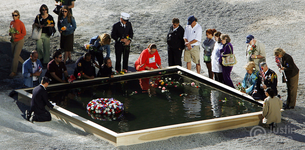 Family members gather at the edge of one of two reflecting pools marking the locations of the World Trade Center towers during the September 11th commemoration ceremony in New York on Monday 11 September 2006. This year marks the five year anniversary of the attacks. ..