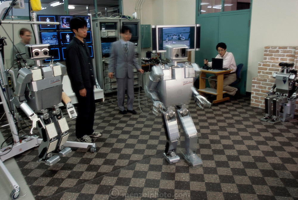 """The H7 robot walks without a safety harness at the Inoue-Inaba Robotics Lab. A joystick operating student, seated at right maneuvers the robot. Research Associate Satoshi Kagami (wearing a suit in the photo) walks with the robot, armed with its """"kill switch"""" in case the robot malfunctions. Its predecessor, H6 hangs at left, near another student who is ready to step in, in the event that the robot falls. The researchers are fairly relaxed during the demonstration compared to those in other labs. University of Tokyo, Japan."""
