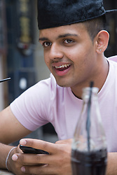 Teenage boy texting on his mobile phone whilst having a drink,