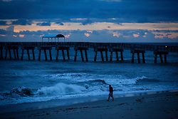 October 7, 2016 - Florida, U.S. - Carlos Melgarejo of Lake Worth takes a walk along the beach in Lake Worth just after dawn Friday, October 7, 2016. He said he came through Hurricane Matthew fine. ''It is a beautiful day,'' he said. ''The water is warm. I came out for the sunrise. Seeing the bands of light through the clouds? Wow, that is magic. There is nothing like Florida. (Credit Image: © Bruce R. Bennett/The Palm Beach Post via ZUMA Wire)