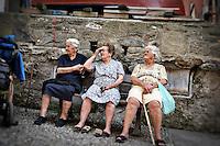 Three elderly women sitting on a bench in Vernazza, Italy.