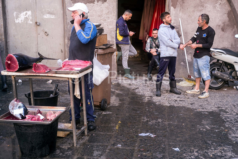 Stallholders at the Mercato della Pescheria Market wait for customers. Catania, Sicily, Italy. A fish market has been held every day in Piazza Alonzo di Benedetto since the beginning of the 19th century, although there has likely been a market here for centuries. and is the most important market in Catania.