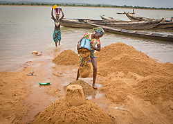 © Licensed to London News Pictures. 05/07/2013. Koulikoro,  Mali.  Mamouna (12) will spend 8 hours a day dredging sand which has been dropped by the workers.  The sand is transported to the shore which is then delivered across Mali for use within the construction industry.   Photo credit: Alison Baskerville/LNP