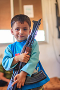 A young boy smiles at the camera and holds the rifle of his uncle to pose for a picture inside Marea's FSA HQ building on Wednesday, June 27, 2012. (Photo by Vudi Xhymshiti)