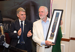 © Licensed to London News Pictures.  25/06/2017; Exeter, Devon, UK. JEREMY CORBYN, the leader of the Labour Party, is presented with a commemorative sash and a t-shirt by RMT General Secretary MICK CASH. Corbyn spoke at the start of the RMT union's annual general meeting in Exeter. Picture credit : Simon Chapman/LNP