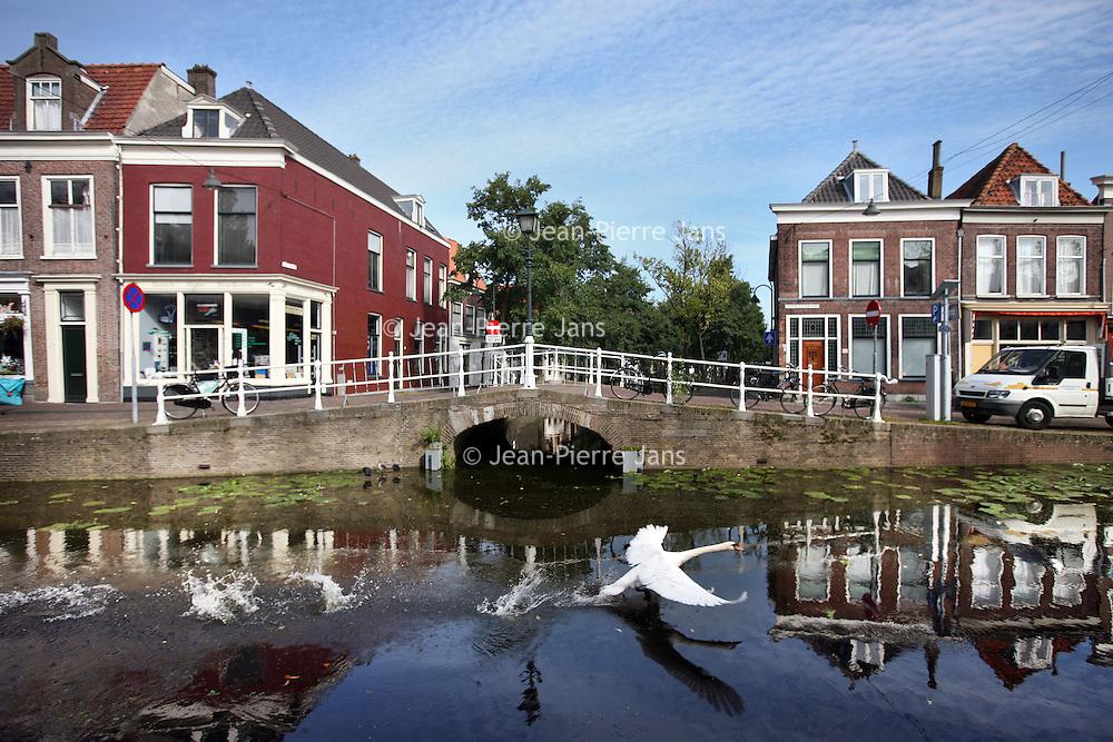 Nederland, Delft , 29 september 2010..Schrijver Kader Abdolah tijdens een wandeling door het centrum van Delft en de Bieslandse Bossen. ..A canal in the historic center of Delft,  the Netherlands