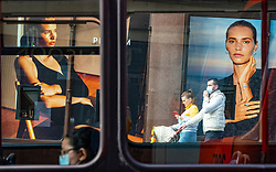 Edinburgh, Scotland, UK. 28 July, 2020. Business and tourism slowly returning to the shops and streets of Edinburgh city centre. View through bus windows of advertising displays in windows of Jenners department store on Princes Street with members of the public wearing face masks. Iain Masterton/Alamy Live News