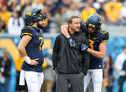 Sep 8, 2018; Morgantown, WV, USA; West Virginia Mountaineers quarterback Will Grier (7) and West Virginia Mountaineers wide receiver David Sills V (13) talk with West Virginia Mountaineers offensive coordinator Jake Spavital before their game against the Youngstown State Penguins at Mountaineer Field at Milan Puskar Stadium. Mandatory Credit: Ben Queen-USA TODAY Sports