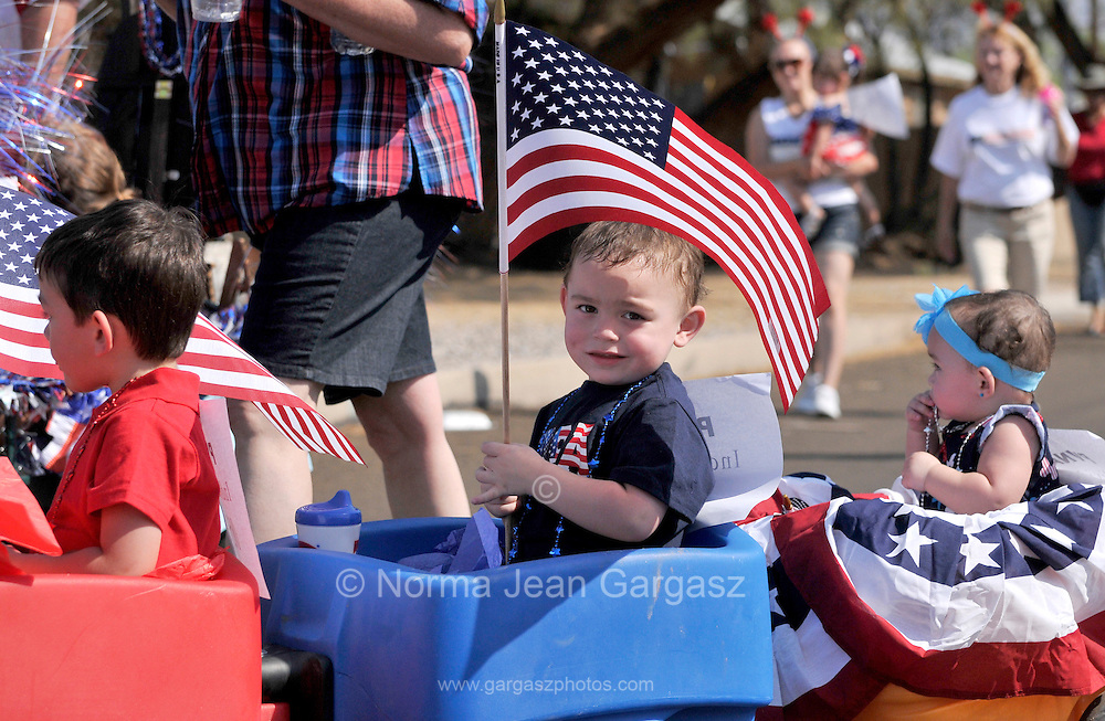 July 4, 2013:  Celebrants in the Palo Verde Neighborhood participate in the 50th annual Fourth of July parade to celebrate the anniversary of the independence of the United States in Tucson, Arizona, USA.  Daniel Brockert-Gonzales, 4, (left), and his brother, Michael, 2, and sister, Lillyana, 2, whose father is deployed in Afghanistan, joins the parade.