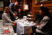 It is tea 4 o'clock and time for cream tea at the Westbury hotel in central London. Served by a waiter who pours from a silver pot into china cups, three ladies enjoy the afternoon after a day's shopping in nearby shopping streets. The decor is classically dark English wood and the tablecloth is crisply white with a scones with jam and sponges.
