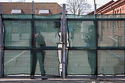 Security guards ready to open the gate to the first taxi arrives of the new intake of asylum seekers arrive at Napier barracks on the 9th of April 2021 in Folkestone, United Kingdom. Despite many criticisms of the site including a damning report from the HM Inspectorate of Prisons declaring the camp filthy and impoverished and Public Health England declaring the accommodation unsuitable durning a pandemic the Home Office continues to place vulnerable people in the former military barracks. (photo by Andrew Aitchison / In pictures via Getty Images)