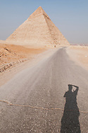 A photographer cast a shadow on an empty road leading to the Pyramid of Khafre (Chephren), built around 2570 BC, in Giza, Egypt.