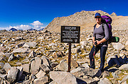 Backpacker and trail sign on Bishop Pass, Kings Canyon National Park, California USA