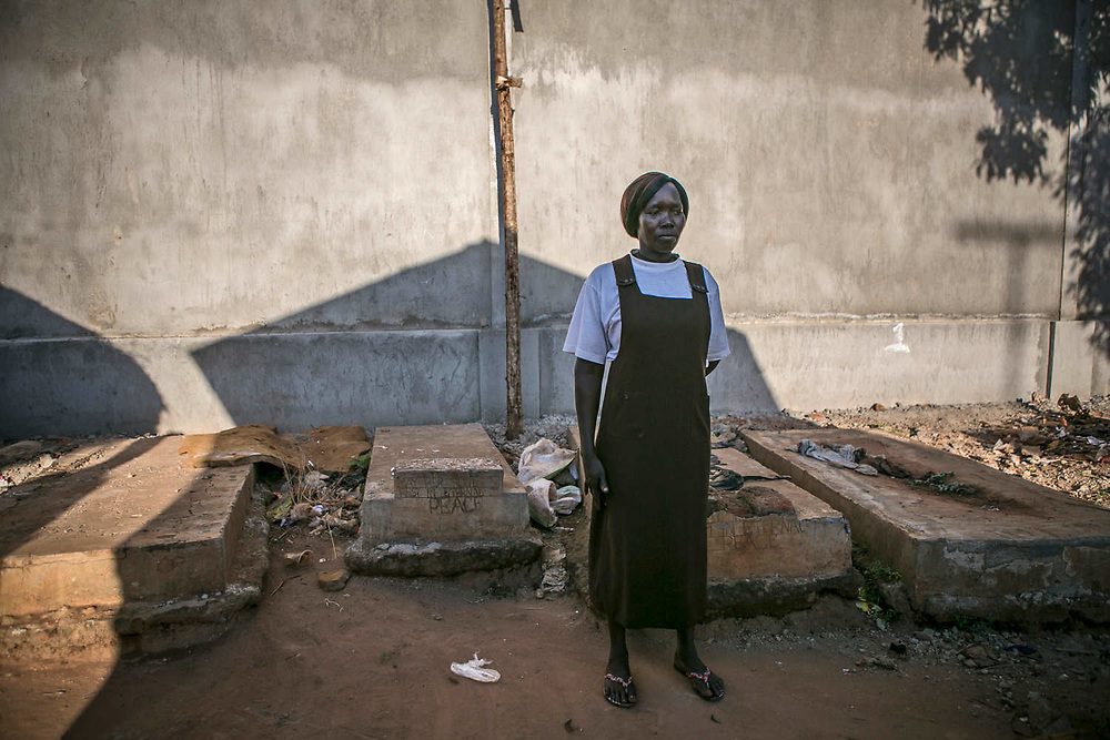 Aciro Scolvia, a former sex slave of LRA, stands in front of her parents' grave in the backyard of her home in Gulu. She said her mother died of frustration and the father died five years after she returned home from abduction. She was abducted by LRA forces in the middle of the night when she was13 years old at St. Mary's school and was assigned to a commander six months later. She became the third wife and gave birth to three children with the commander, who had at least 13 children from three wives, including her. Scolvia stayed 9 or 10 years in the bush and escaped.