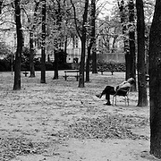 An elderly gentleman sleeps in the open space of the Jardin du Luxembourg  in Paris, France. October 14, 2007. Photo Tim Clayton.. Paris is often known as 'The City of Love' but like any major City in the world, the inhabitants often live a singular existence, going about their daily lives in relative solitude. Parisians are respectful of each others space, often courteous and polite while extremely conscious of their own image. While love can be seen openly around the streets of Paris, so can the separate lives of Parisians.