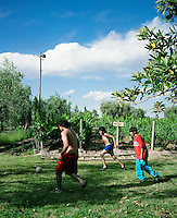 Young boys play a pick-up game of soccer in front of Malbec vines at Finca La Heredad in the Luján de Cuyo area of Mendoza, Argentina. The  farm's vines surround the boutique hotel Club Tapiz.