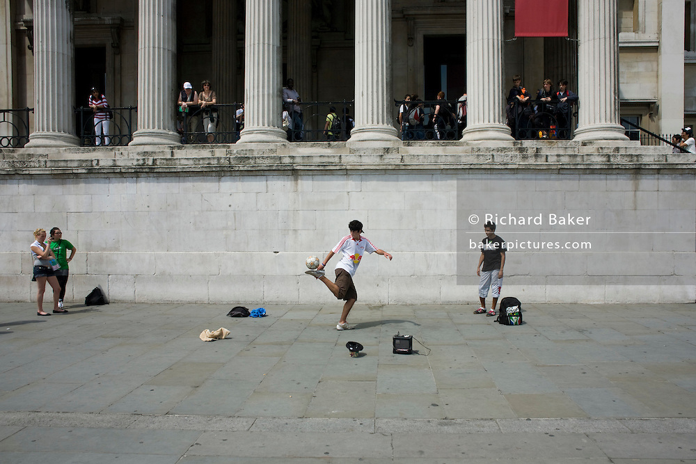 A young busker performs football skills on the pavement outside the National Portrait Gallery.