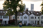 A woman park user drinks from a plastic water bottle in front of suburban houses in Ruskin Park, on 7th June 2021, in south London, England.