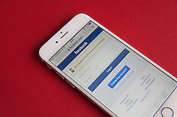 Gold and white Apple iPhone 6 with Facebook log in screen against a red background