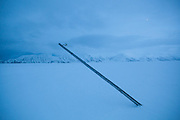 Abandoned and leaning utility pole on Sverdruphamaren, Svalbard.