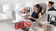 photographie corporate montrant une jeune femme d'origine asiatique prenant un thé pendant son vol, confortablement installé en classe business de la compagnie aérienne Aircalin.