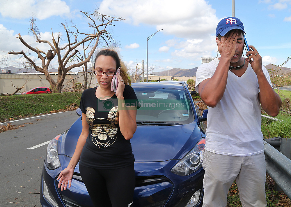 October 2, 2017 - Miami, Florida, U.S. - CARLOS ROLAN, a financial planner and his wife NERYS MEDINA, from the town of San Lorenzo, stop along the Caguas road to call their relatives in Orlando Florida to communicate to them their decision to leave Puerto Rico on Oct. 22nd. It is a decision against their will since their house got damaged, he is jobless and their daughters' schools are closed for an unknown amount of time forcing many Puerto Ricans to fly to the U.S. after Hurricane Maria, (category 4) passed through Puerto Rico devastating the island leaving residents without power and ways to communicate.. (Credit Image: © Pedro Portal/TNS via ZUMA Wire)