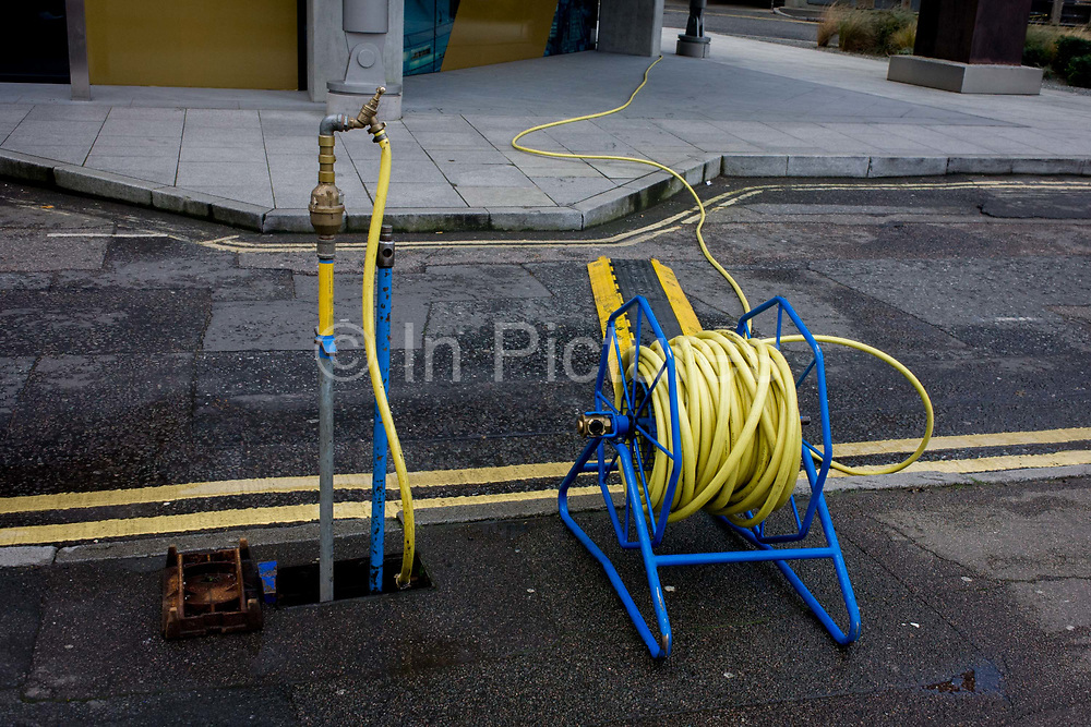 Yellow hosepipe streched across road with coincidental double-yellow lines. Watering an unseen feature in this urban landscape, we see the repetition of colour across the road and into the distance. The picture suggests a quirky urban humour - a coincidence of lines and color.