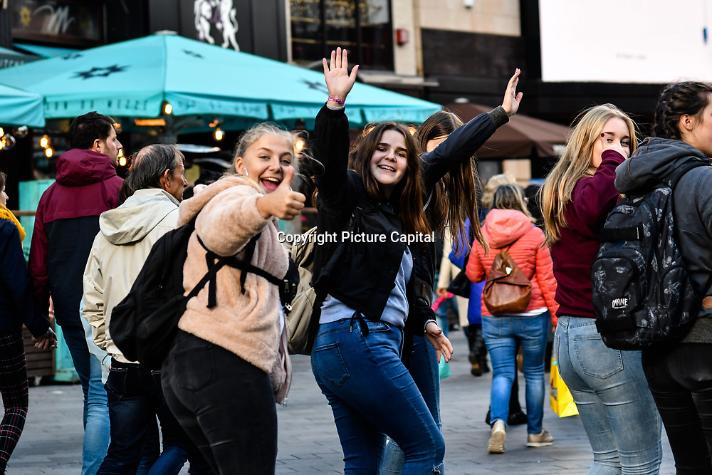 Tourist smiling at the photographer walking pass at Leicester Square, London, UK 23 September 2018.