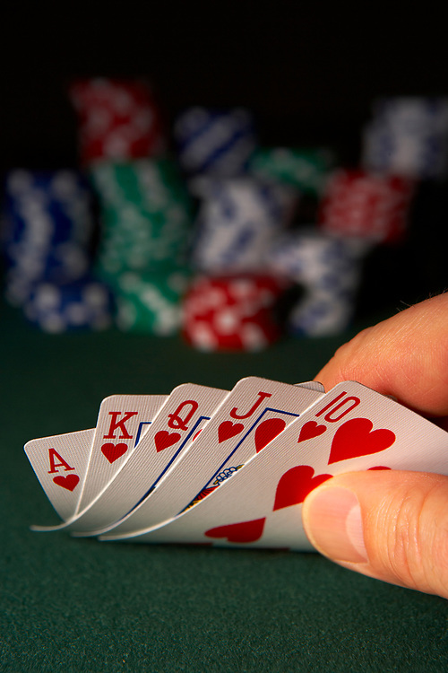 Hand exposing royal flush poker hand with out of focus poker chips in background