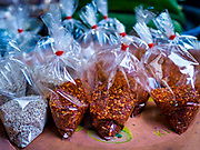 20 JUNE 2018 - BANGKOK, THAILAND: Flaked chilies and other seasonings in plastic bags at Makkasan Market, a small local market in central Bangkok. Officials in Thailand are wrestling with Thais use of plastic bags. The issue became a public one in early June when a whale in Thai waters died after ingesting 18 pounds of plastic. In a recent report, Ocean Conservancy claimed that Thailand, China, Indonesia, the Philippines, and Vietnam were responsible for as much as 60 percent of the plastic waste in the world's oceans.     PHOTO BY JACK KURTZ