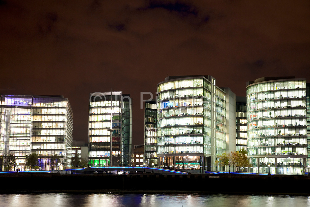 Night scene looking over the River Thames towards the skyline of More London area offices and business district. This area is a recent development which is now thriving and bustling with more buildings being constructed in this moderm glass style and filling the area with office workers.