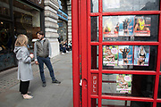 People passing a public telephone box which has sex cards tacked up inside on Piccadilly in London, United Kingdom. These advertising cards for prostitutes are how people advertise for sexual services under the guise of other services like massage for example.