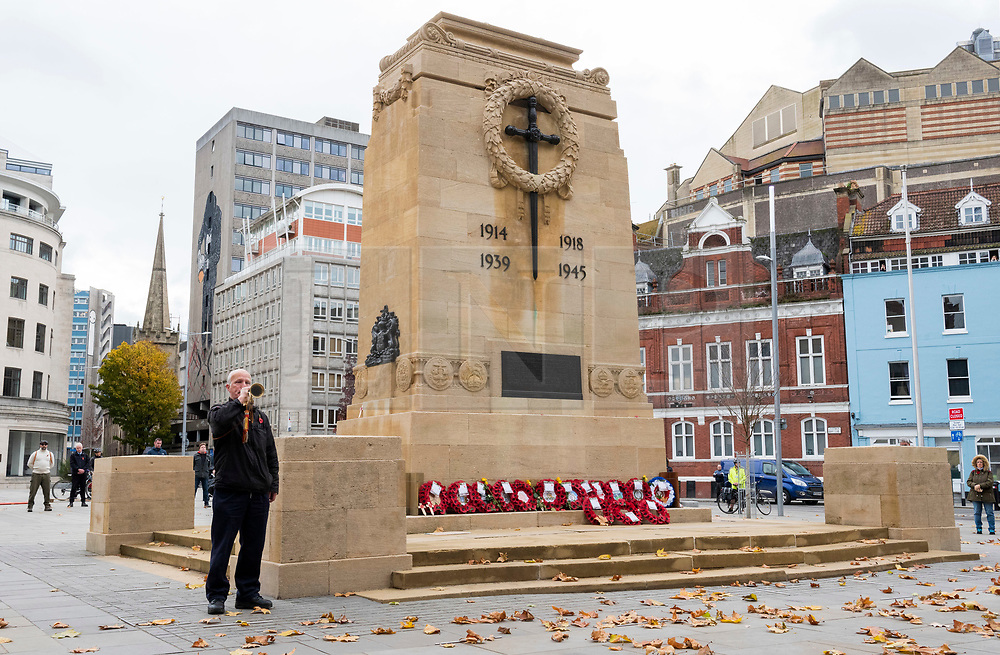 """© Licensed to London News Pictures; 11/11/2020; Bristol, UK. Remembrance Day at the Bristol Cenotaph in the city centre. ALLAN MARSH from Bristol and retired from the Fire Service, plays the tune of the Last Post on his bugle in memory of his father. The normal large military parade and civic procession was cancelled due to the national lockdown restrictions for the Covid-19 coronavirus pandemic, but around 40 people gathered for the two-minute silence that traditionally takes place at 11.00am, recognising the precise time that the hostilities ceased in 1918 – the 11th hour of the 11th day of the 11th month. ALLAN MARSH (contact details available), from Bristol and retired from the Fire Service, plays the tune of the Last Post on his bugle at the Cenotaph in memory of his father Colour Sergeant Arthur Henry Marsh (1908 - 1976) who served during World War Two in the 10th Battalion of the Gloucestershire Regiment in Burma, Malaya, Singapore and India. The Fourteenth Army 1942 -1945 was known as the """"Forgotten Army"""". Having defeated the Japanese invasion of India in 1944 they fought on after the war in Europe ended to liberate Burma (now Myanmar) in 1945. The Fourteenth Army was the British army's most diverse and multicultural army with many faiths and nationalities including Gurkhas and Sikh soldiers fighting for the UK against Japan. It was led by Field Marshal Sir William Slim who was born in Bristol. Photo credit: Simon Chapman/LNP."""