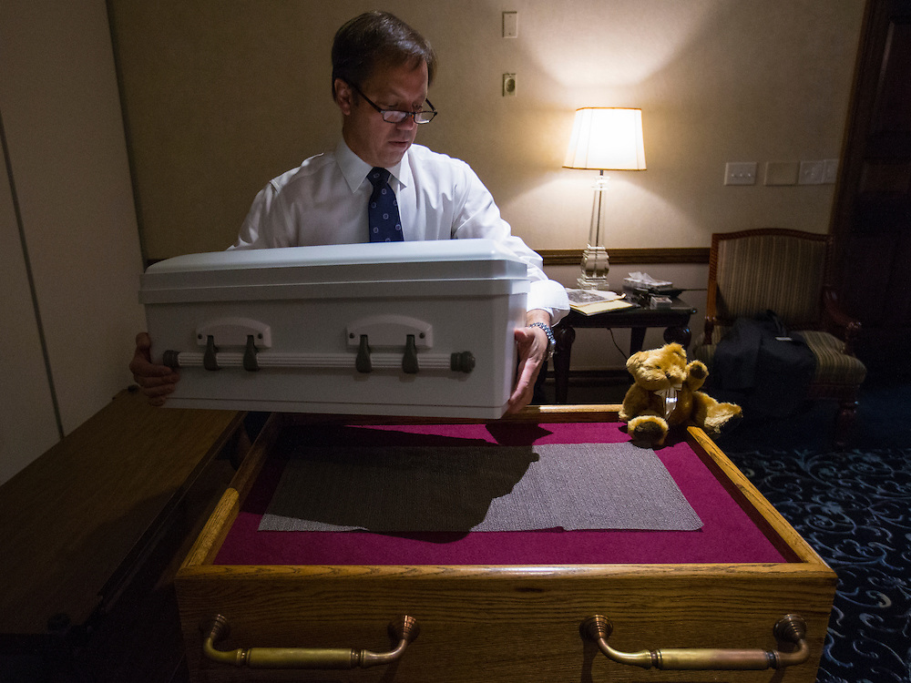 """Glueckert Funeral Home Funeral Director John Glueckert lifts the casket containing the remains of an abandoned newborn baby on to a table in preparation for funeral and burial services in Arlington Heights, Illinois, United States, June 19, 2015. More than a year after he was found dead in a plastic shopping bag on a Chicago sidewalk, the baby boy was buried by a non-profit group """"Rest in His Arms"""" after being abandoned by his teenage mother, who is charged with murder.  REUTERS/Jim Young"""