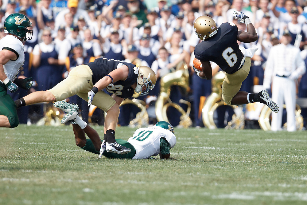 Notre Dame wide receiver Theo Riddick (#6) is tripped up by South Florida defender Terrence Mitchell (#10) in action during NCAA football game between Notre Dame and South Florida.  The South Florida Bulls defeated the Notre Dame Fighting Irish 23-20 in game at Notre Dame Stadium in South Bend, Indiana.