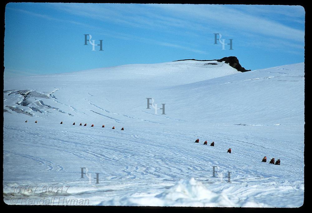 Line of snowmobiles trails up distant slope atop Vatnajokull glacier during a two-hour Glacier Tours trip; southeast Iceland.