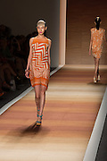 An orange print sleeveless dress with dip hem.