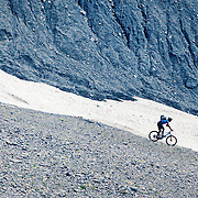 A man cycling below the Eiger Glacier (Eigergletscher) in the Bernese Alps, Switzerland.<br />