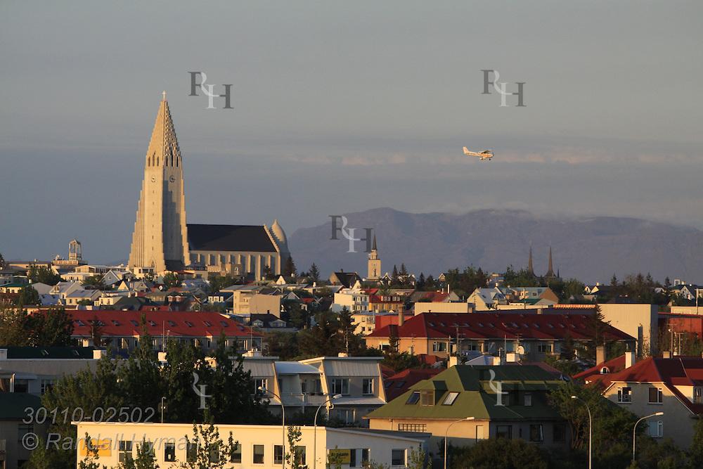 On a June evening the steeple of Hallgrimskirkja towers over skyline of Reykjavik, Iceland.