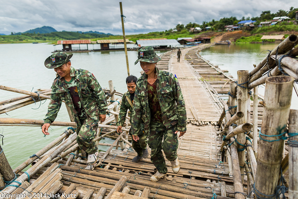 17 SEPTEMBER 2014 - SANGKHLA BURI, KANCHANABURI, THAILAND: Thai soldiers walk along the temporary bamboo bridge the Mon community is using while the Mon Bridge, in the background, is being repaired. The 2800 foot long (850 meters) Saphan Mon (Mon Bridge) spans the Song Kalia River. It is reportedly second longest wooden bridge in the world. The bridge was severely damaged during heavy rainfall in July 2013 when its 230 foot middle section  (70 meters) collapsed during flooding. Officially known as Uttamanusorn Bridge, the bridge has been used by people in Sangkhla Buri (also known as Sangkhlaburi) for 20 years. The bridge was was conceived by Luang Pho Uttama, the late abbot of of Wat Wang Wiwekaram, and was built by hand by Mon refugees from Myanmar (then Burma). The wooden bridge is one of the leading tourist attractions in Kanchanaburi province. The loss of the bridge has hurt the economy of the Mon community opposite Sangkhla Buri. The repair has taken far longer than expected. Thai Prime Minister General Prayuth Chan-ocha ordered an engineer unit of the Royal Thai Army to help the local Mon population repair the bridge. Local people said they hope the bridge is repaired by the end November, which is when the tourist season starts.    PHOTO BY JACK KURTZ