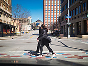 """29 MARCH 2020 - DES MOINES, IOWA: A couple crosses an empty street in downtown Des Moines. On Sunday morning, 29 March, Iowa reported 336 confirmed cases of the Novel Coronavirus (SARS-CoV-2) and COVID-19. There have been four deaths attributed to COVID-19 in Iowa. Restaurants, bars, movie theaters, places that draw crowds are closed until 07 April. The Governor has not ordered """"shelter in place""""  but several Mayors, including the Mayor of Des Moines, have asked residents to stay in their homes for all but the essential needs. People are being encouraged to practice """"social distancing"""" and many businesses are requiring or encouraging employees to telecommute.        PHOTO BY JACK KURTZ"""