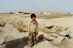 A dirty barefoot Iraqi boy of about 5 years old stands for his photograph taking amid the desolate landscape of the Basra region of Iraq in March 2005.