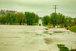 30 Apr 2019: Muddy water rolls as the Kickapoo Creek overflows its banks and into the flood plane west and a semi truck manages to ford the mess of Heyworth in McLean County Illinois