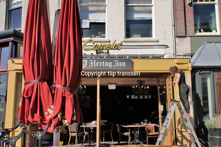 Nederland, Nijmegen, 25-4-2020  Bij een cafe in het centrum van de stad is personeel bezig met het schilderen , opknappen, van de buitenkant. de horeca is al enkele weken gesloten vanwege de coronadreiging en veel ondernemers willen dat de regering het normale dagelijks leven weer langzaam laat opstarten . Unlock,beperkende,opheffen,versoepelen,versoepeling . Foto: Flip Franssen