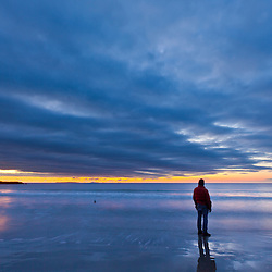 A man looks at dawn, Wallis Sands State Park, Rye, New Hampshire.