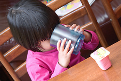 Little girl having a drink from a plastic cup,